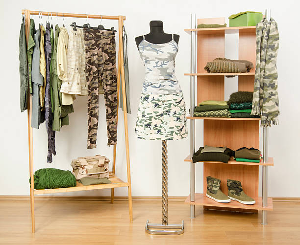 Wardrobe with camo pattern clothes and accessories. stock photo