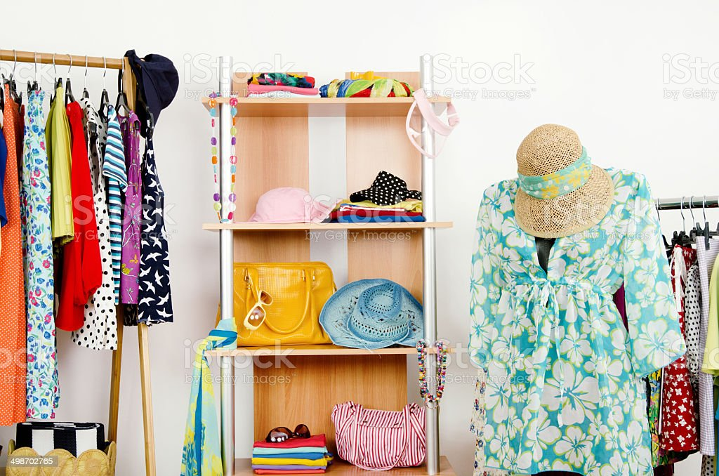 Wardrobe with summer clothes and a beach outfit on mannequin. stock photo