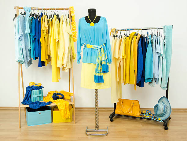 Wardrobe with yellow and blue clothes arranged on hangers. stock photo