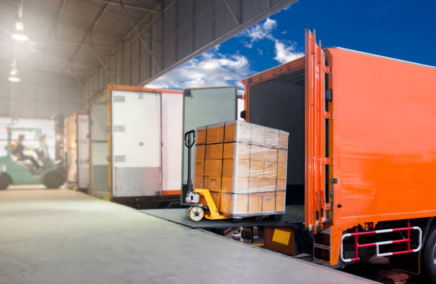Warehouse and logistics, freight transportation. Trucks docking at warehouse and forklift driver loading cargo into container. pallet jack stock pictures, royalty-free photos & images