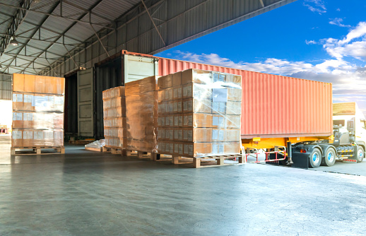 Freight transportation by trucks, trucks trailer docking loading cargo at warehouse