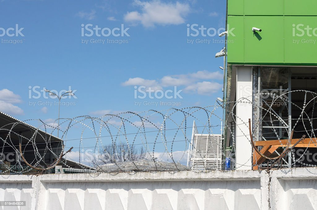 Warehouse behind the fence with barbed wire stock photo