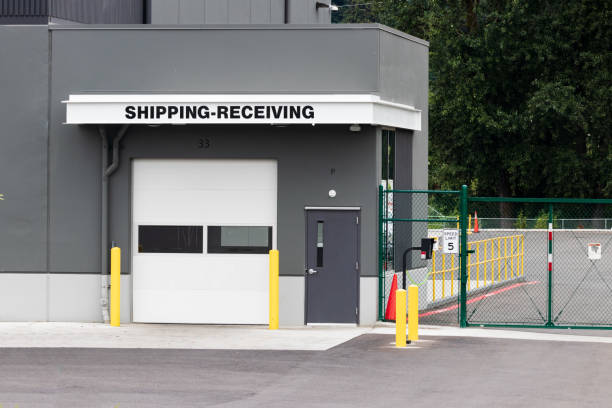 Warehouse building shipping receiving garage door and gate with road driveway stock photo