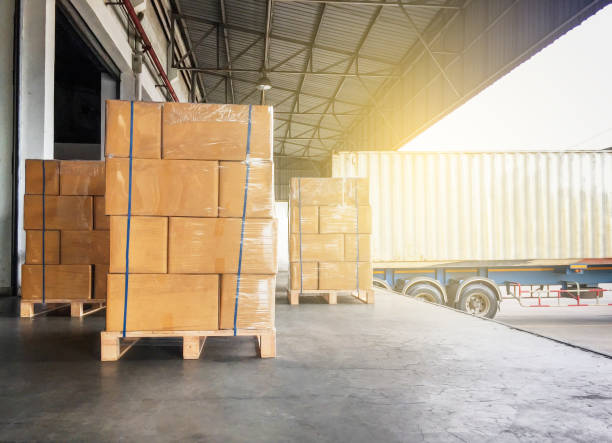 warehouse cargo courier shipment. stack of cardboard boxes on wooden pallet and truck docking at warehouse - logistica foto e immagini stock