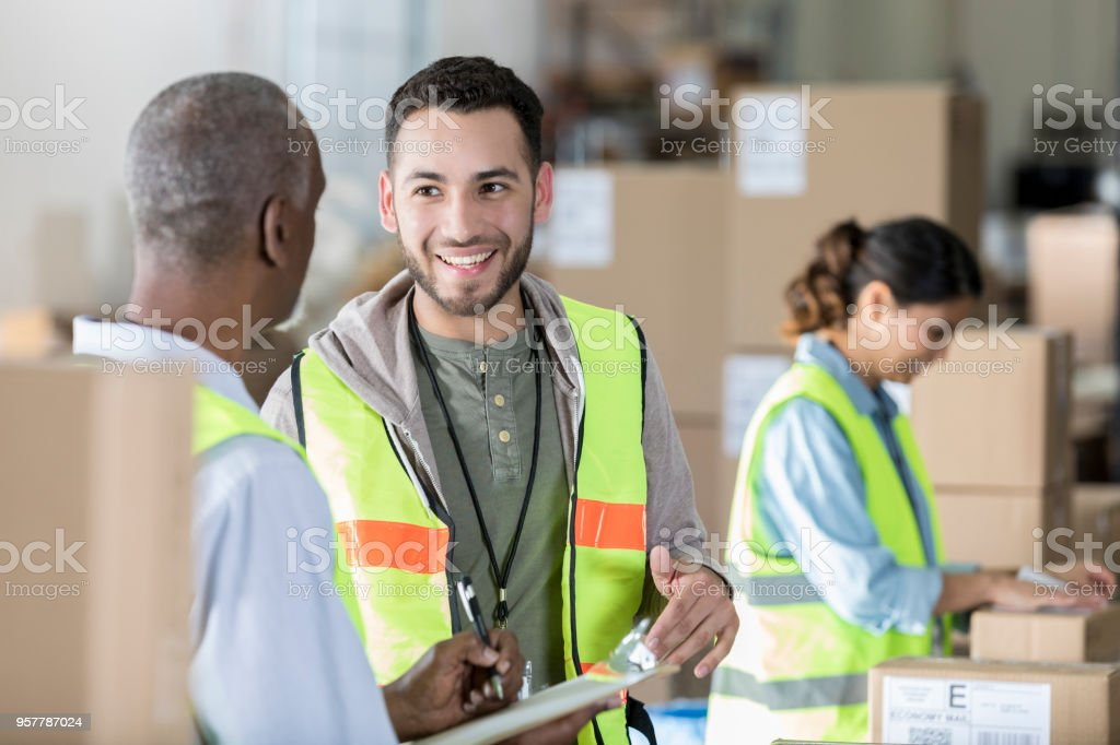 Warehouse co-works discuss customer order stock photo