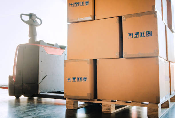 Warehouse distribution with electric forklift Electric forklift pallet jack with stack of cardboard boxes on wooden pallet pallet jack stock pictures, royalty-free photos & images