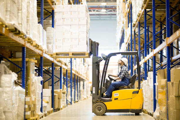 Warehouse driver operating forklift stock photo