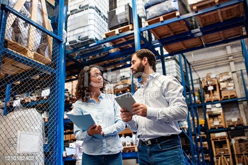 Manager with female colleague taking inventory in company warehouse. Warehouse employees checking stock levels in store room.
