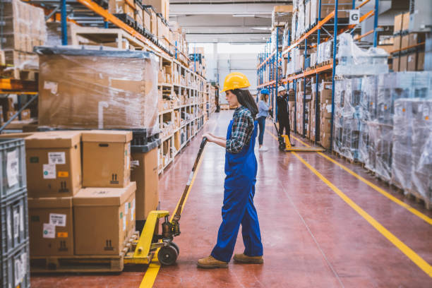 Warehouse employees working with boxes Manual workers and technician checking and carrying boxes down with pallet car or handling mechanical industrial jacks  in the large distrubition warehouse corridor in factory building. pallet jack stock pictures, royalty-free photos & images
