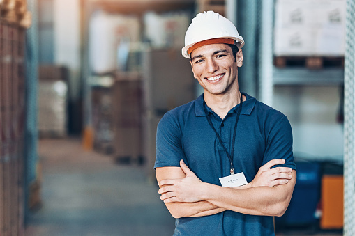 Portrait of a smiling young man with protective helmet in a warehouse