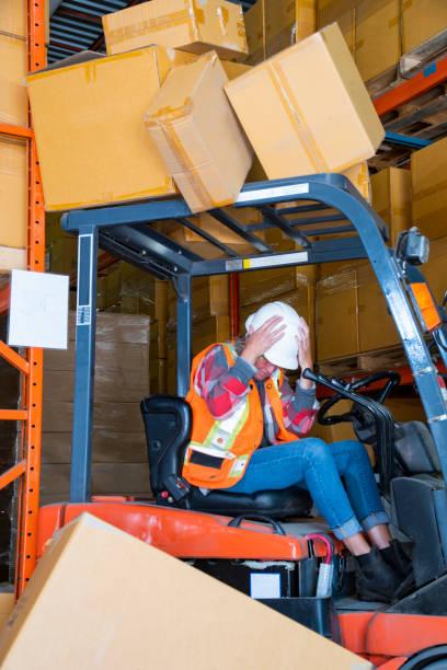 Ein Lagergabelstapler-Sicherheitsthema.  Ein Gabelstaplerfahrer kehrt in ein Regal, in dem auf den Gabelstapler fällt. – Foto