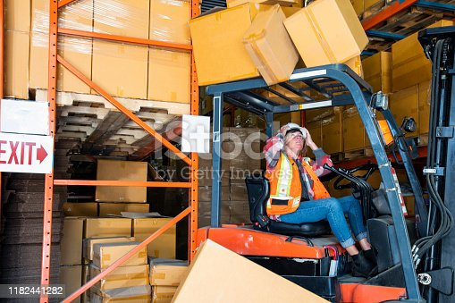 A warehouse forklift safety topic.  A forklift driver dangerously reverses into a shelf knocking boxes of that fall onto the forklift risking serious injury. Purposeful motion blur.