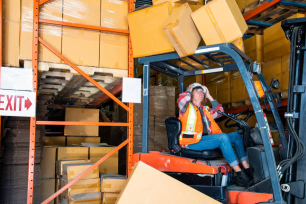 A warehouse forklift safety topic.  A forklift driver reverses into a shelf knocking boxes of that fall onto the forklift. stock photo