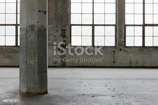 Empty industrial warehouse with concrete columns and large vintage windows.