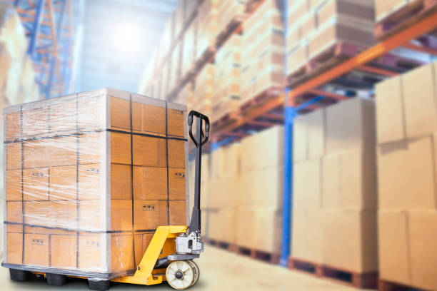 Warehouse inventory and cargo in warehouse Hand pallet truck or pallet jack with stacked cardboard boxes on pallet, cargo storage on tall shelves in warehouse pallet jack stock pictures, royalty-free photos & images