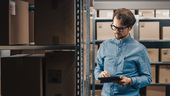 Warehouse Inventory Manager Uses Tablet Computer To Check