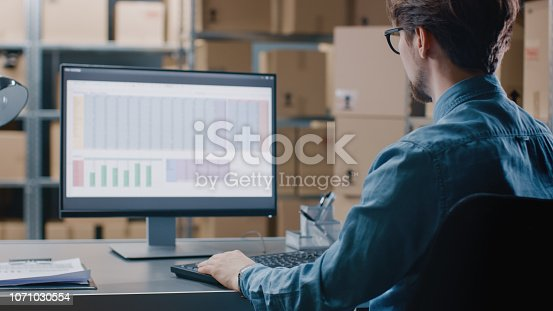 Warehouse Inventory Manager Works with a Spreadsheet on a Personal Computer while Sitting at His Desk. In the Background Shelves Full of Cardboard Box Packages Ready For Shipping.