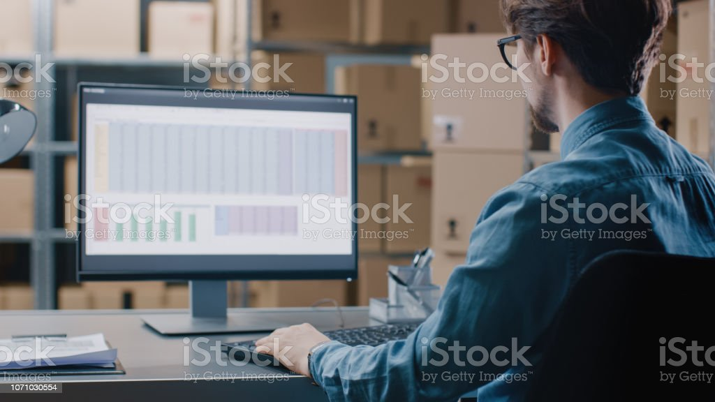Warehouse Inventory Manager Works with a Spreadsheet on a Personal Computer while Sitting at His Desk. In the Background Shelves Full of Cardboard Box Packages Ready For Shipping. stock photo