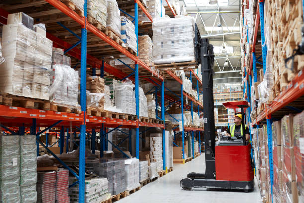 Warehouse logistic center. Worker driving on a forklift Warehouse interior. Using forklift pallet jack stock pictures, royalty-free photos & images