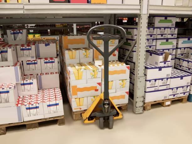 warehouse / logistics / commerce lifting cart in a high rack warehouse pallet jack stock pictures, royalty-free photos & images