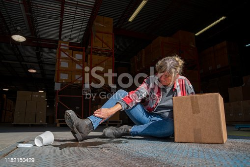 A warehouse, logistics safety topic.  A female employee falls after slipping on a spilled drink.  Slips, trips and falls are a major cause of injuries in industrial workplaces.