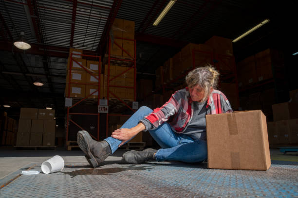 A warehouse, logistics safety topic.  A female employee falls after slipping on a spilled drink. stock photo
