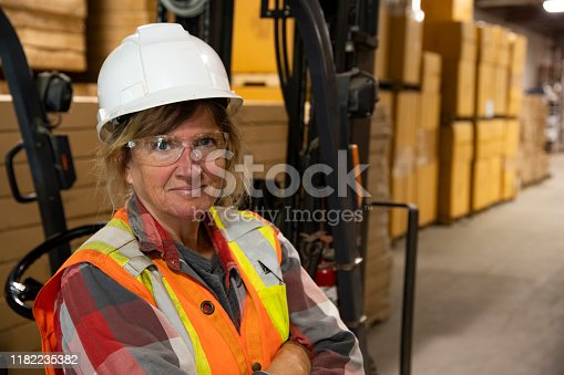 A warehouse, logistics safety topic.  A female employee looking confident pensive beside a forklift.