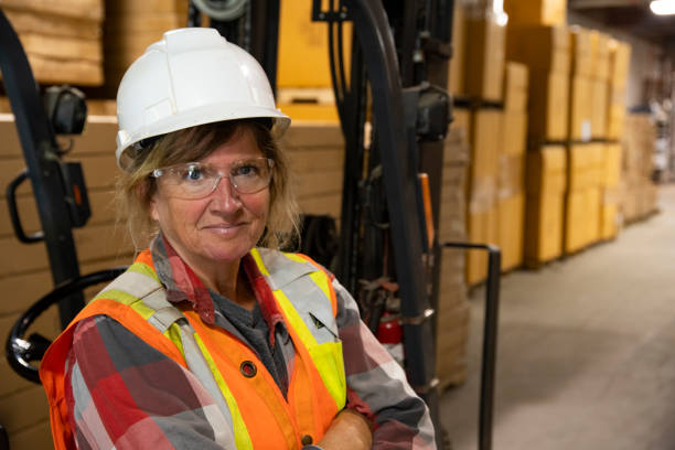 A warehouse, logistics safety topic.  A female employee looking confident beside a forklift. stock photo