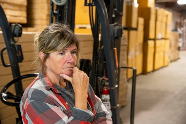 A warehouse, logistics safety topic.  A female employee looking depressed or pensive beside a forklift. stock photo