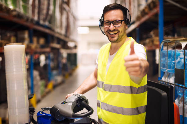 warehouse man worker in vorkheftruck holding thumbs up. distributiemagazijn medewerker met headset voor communicatie organiseren van goederenlevering. - warehouse worker stockfoto's en -beelden