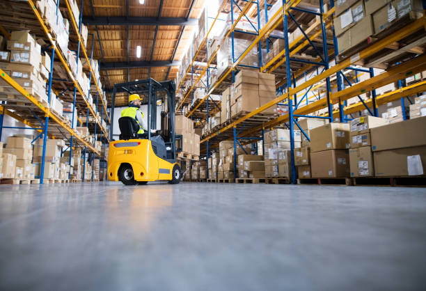 Warehouse man worker with forklift. Young male worker lowering a pallet with boxes. Forklift driver working in a warehouse. warehouse interior stock pictures, royalty-free photos & images