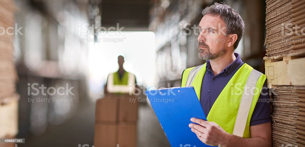 warehouse manager checking deliveries on his laptop stock photo