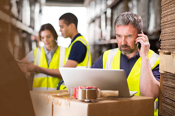warehouse manager ringing a supplier stock photo
