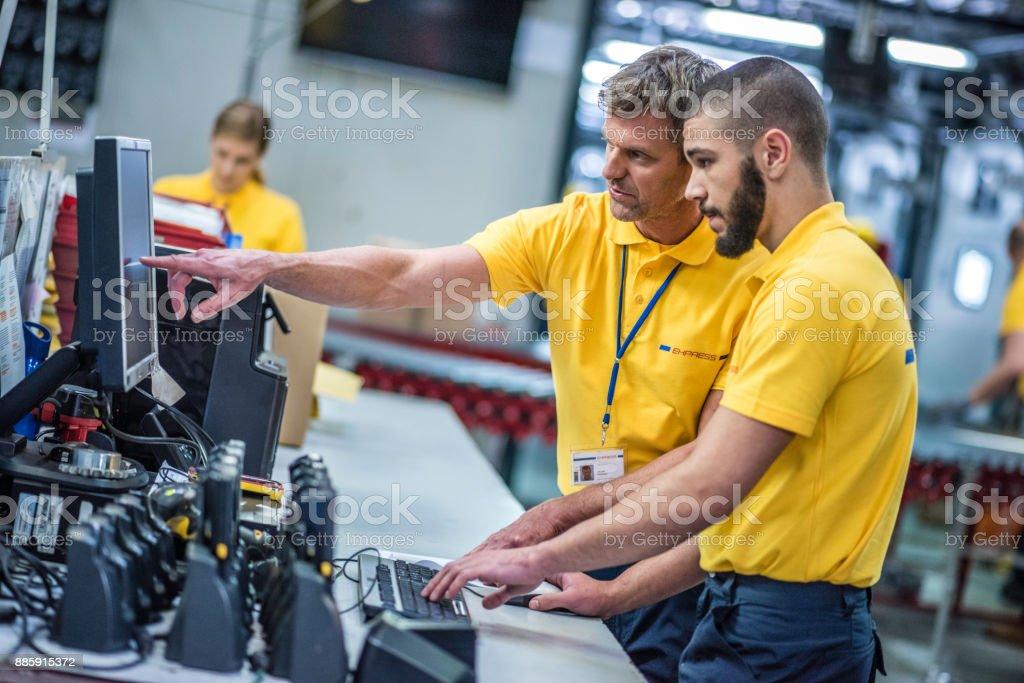 Lagerleiter anzeigen Mitarbeiter etwas auf dem PC – Foto