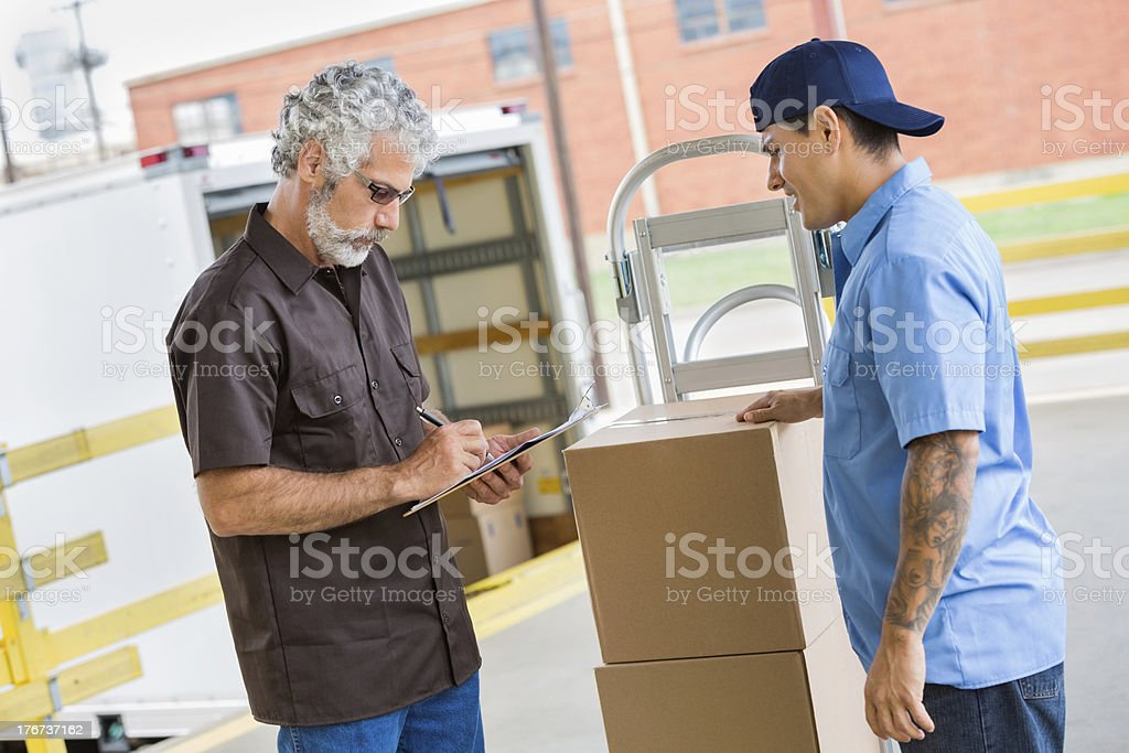 Warehouse manager signing for packages being delivered royalty-free stock photo