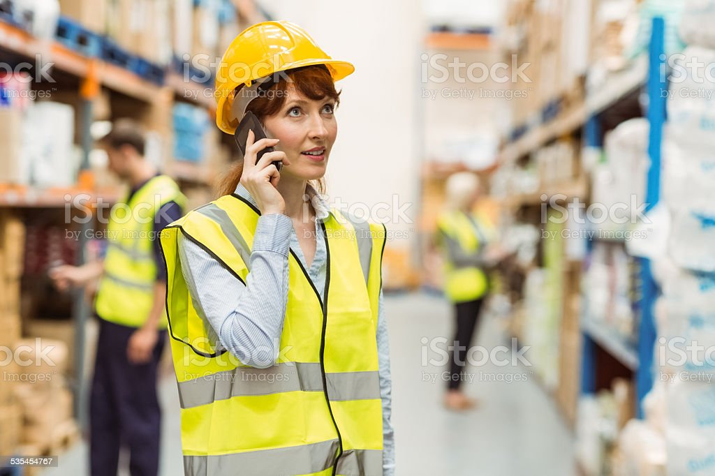 Warehouse manager talking on the phone looking around stock photo