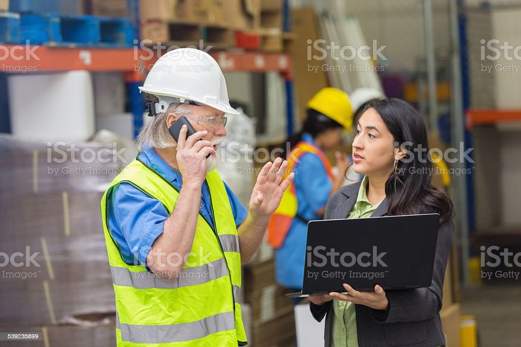 Warehouse manager talking to client while using laptop with supervisor royalty-free stock photo