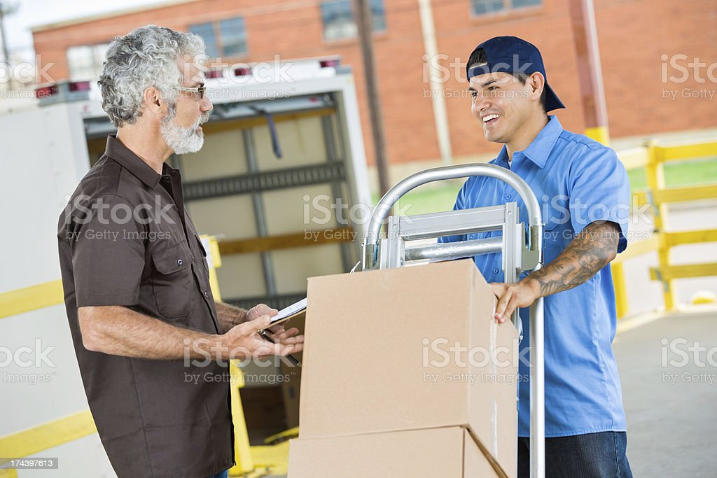 Warehouse manager talking with delivery driver royalty-free stock photo