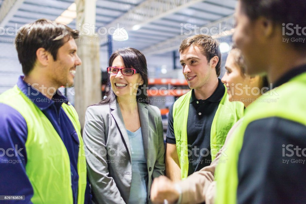 Warehouse manager talking with workers stock photo