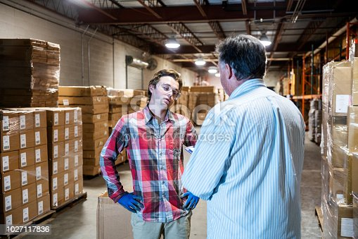 A mature warehouse manager discusses issues with a younger male warehouse worker.  The young worker has a look of disagreement and annoyance.  The manager is raising job performance or safety issues with the young man.
