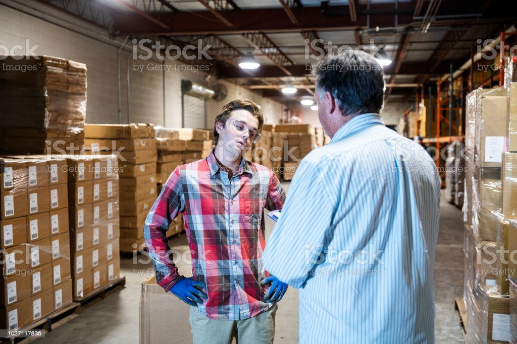 A warehouse manager talks with a younger warehouse worker. stock photo