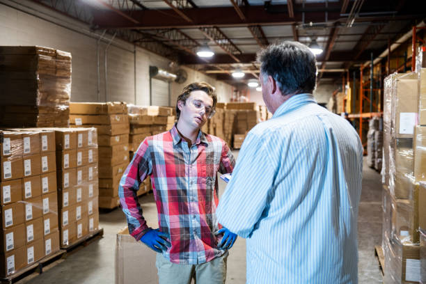 A warehouse manager talks with a younger warehouse worker. A mature warehouse manager discusses issues with a younger male warehouse worker.  The young worker has a look of disagreement and annoyance.  The manager is raising job performance or safety issues with the young man. punishment stock pictures, royalty-free photos & images