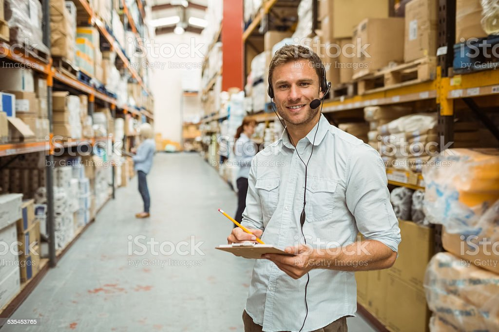 Warehouse manager wearing headset writing on clipboard Warehouse manager wearing headset writing on clipboard in a large warehouse 2015 Stock Photo