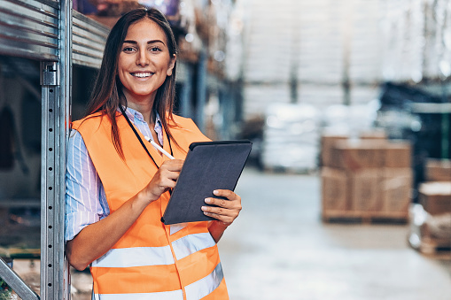 Smiling young woman with digital tablet in a large warehouse