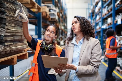 Manager with foremen controlling stock in warehouse. Warehouse worker pointing at the rack with a businesswoman holding a clipboard.