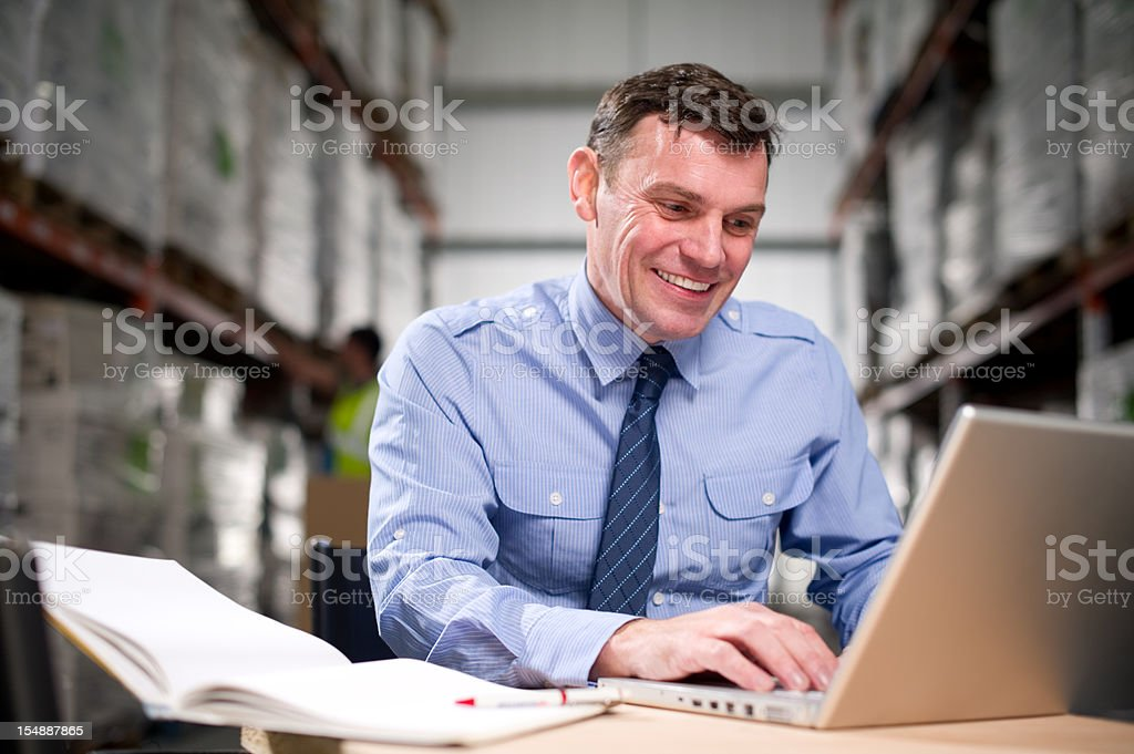 Warehouse Manager Working on a Laptop royalty-free stock photo