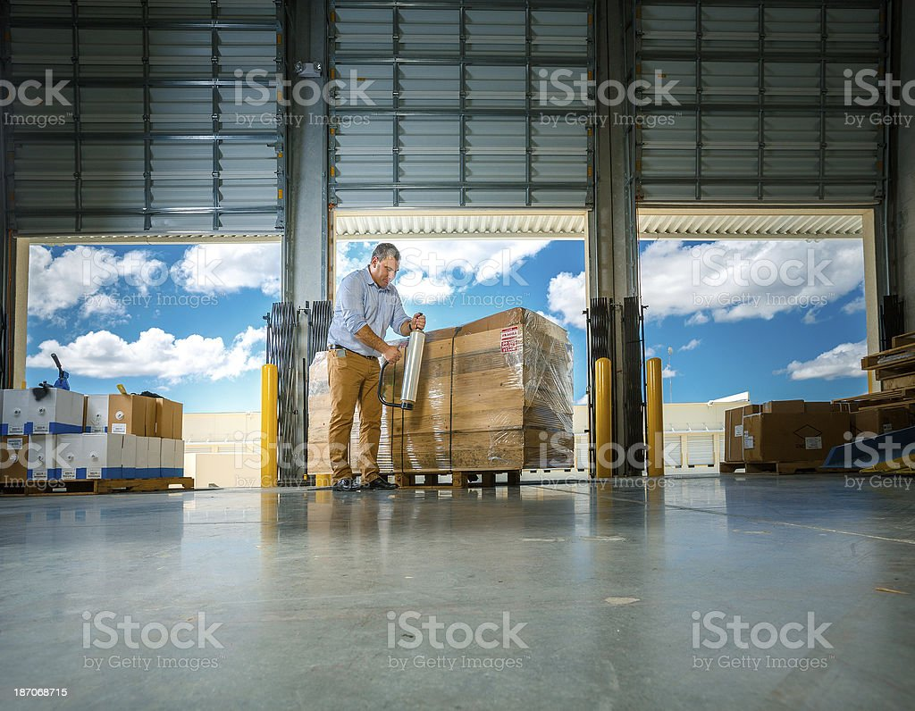 warehouse manager wrapping merchandise stock photo