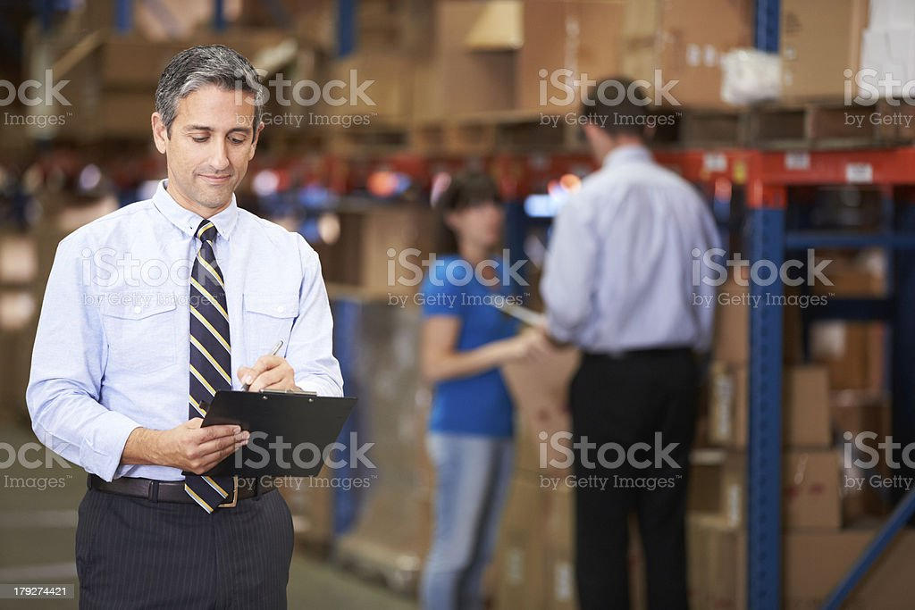 Warehouse manager writing on clipboard royalty-free stock photo