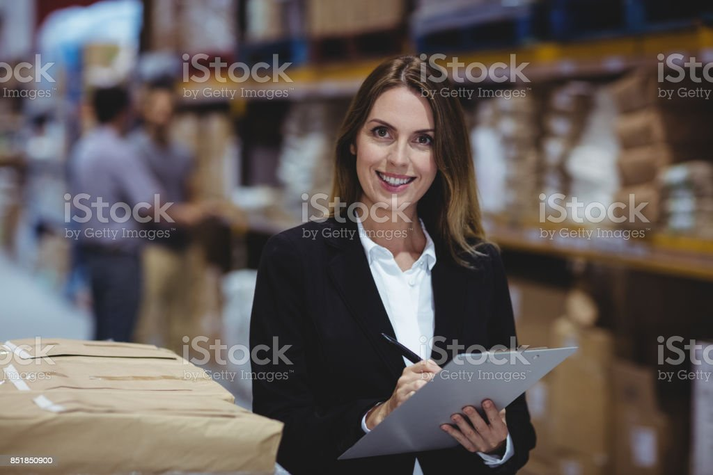 Warehouse manager writing on clipboard stock photo