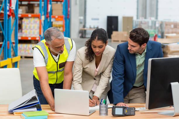 lagerleiter und arbeiter diskutieren mit laptop - lehnend stock-fotos und bilder
